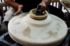 Classic making a pottery bowl on the pottery wheel. A woman is throwing a marl clay on the pottery wheel. She uses an equipment to make a shape of bowl. This is Royalty Free Stock Photos