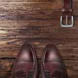 Classic male brown leather shoes with belt on wood Royalty Free Stock Image
