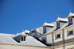 Classic mansard roofing. Exterior mansard roof with a series of windows Royalty Free Stock Photography