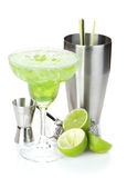 Classic margarita cocktail with salty rim, limes and drink utensils Stock Photography