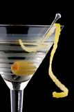 Classic martini - Most popular cocktails series. Classical martini in chilled glass over black background on reflection surface, garnished with olive and lemon Royalty Free Stock Images