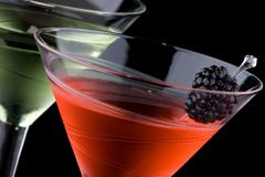 Classic martini - Most popular cocktails series. Classical martini in chilled glass over black background on reflection surface, garnished with fresh blackberry Royalty Free Stock Photo