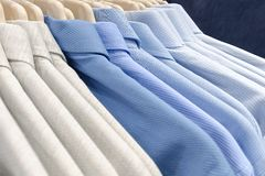 Classic men`s shirts made of cotton light cool tones on the clothes hanger in the store. Selling wear in blue color. Photo with shallow depth of field Royalty Free Stock Image