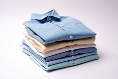 Classic men`s shirts stacked on white background. Classic men`s shirts stacked on white background Royalty Free Stock Photo