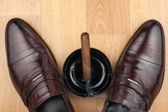 Classic men's shoes, ashtray and  fuming cigar on the wooden flo Royalty Free Stock Images