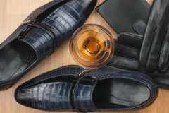 Classic men`s shoes and glass of cognac, gloves and purse on wooden desk. View from above Stock Photo