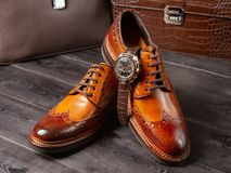 Classic men`s shoes of a light brown shade against the background of men`s leather briefcases royalty free stock images