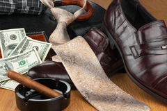 Classic men's shoes, money, tie, umbrella, cigar, ashtray and  bag on the wooden floor Royalty Free Stock Images