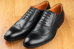 Classic men's shoes stand on the wooden floor Royalty Free Stock Photography
