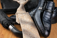 Classic men's shoes, tie, umbrella  and bag on the wooden floor Royalty Free Stock Photos