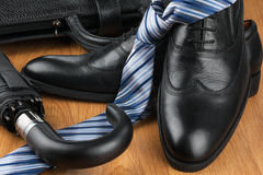 Classic men's shoes, tie, umbrella and bag on the wooden floor Stock Photos