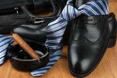 Classic men's shoes, tie, umbrella, cigar, ashtray  and bag on t. He wooden floor, can be used as background Stock Images