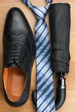 Classic men's shoes, tie, umbrella on the wooden floor Stock Photo