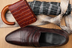 Classic men's shoes, tie, wallet, umbrella on the wooden floor Royalty Free Stock Photography