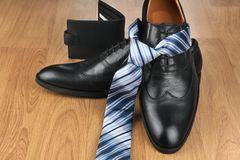 Classic mens black shoes, tie, purse, on wooden floor. Men`s fashion and lifestyle Stock Photo