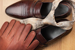 Classic mens brown shoes, tie, gloves, on wooden floor. Can be used as background Royalty Free Stock Photos