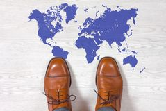 Classic mens shoes with a world map outline on the floor Royalty Free Stock Photo