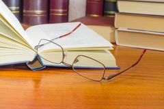 Eyeglasses against of the open book and other books closeup. Classic mens eyeglasses and open book in blue hardcover on a wooden table closeup against of the Stock Images