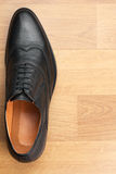 Classic mens shoes stand on the wooden floor. With place for your text Royalty Free Stock Image