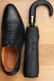 Classic mens shoes and  umbrella  on the wooden floor Stock Images