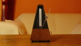 Classic metronome clicking. In warm toned light stock video