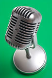 Classic microphone on green background. Classic microphone isolated over white Royalty Free Stock Photos