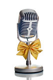Classic microphone isolated. Classic microphone with golden bow tie isolated over white Royalty Free Stock Photos