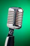 Classic microphone isolated on green background. In vertical composition Royalty Free Stock Photography