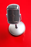 Classic microphone on red background. Classic microphone isolated over white Stock Photo