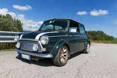Classic Mini Cooper. A british green Mini Cooper with white stripes on the roof on a sunny day Royalty Free Stock Photography