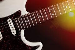 Live music. Modern electric guitar close-up with stage lights. Classic modern electric guitar close-up of fingerboard frets and body with pick-up. Live country stock image
