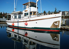 Classic motor yacht in marina. White classic wooden motor yacht and its reflection on calm waters of Des Moines, Washington marina Stock Photos