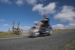 Classic motorcycle speeding on mountain road Royalty Free Stock Images