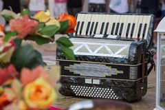 Classic musical instrument an accordion in black color, with flowers on the stage stock images