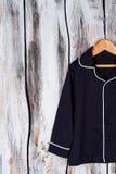 Classic navy pajama shirt. Unisex sleeping garment on wooden hanger. Sleepwear and robes Stock Image