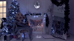 Classic New year and christmas background, evening view with lamp light, flashing garland and candles on the artificial fireplace. stock video