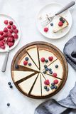 Classic New York cheesecake with fresh berries, top view. Classic New York cheesecake with fresh raspberries and blueberries on white concrete background, top Stock Photo