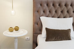 Classic Nightstand With Lamp. Classic white nightstand with a amp next to a bed with velvet headboard Stock Photography