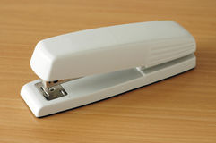 Classic office stapler. A white office stapler on a wooden desktop stock image