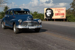 Classic old American car and Che portrait. VINALES, CUBA, FEBRUARY 20, 2014 : Classic old American car and a Che Guevara poster. Classic cars are still in use in stock photo