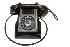 Classic old black rotary dial-up telephone. Instrument, closeup frontal view with the handset in place over a white studio background royalty free stock photo