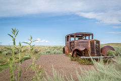 Classic Old Car decays in a meadow. Royalty Free Stock Photo