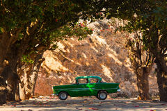 Classic old car under trees in Cuba Royalty Free Stock Images