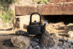 Classic old kettle with black soot on pile of stones at camping. With nature background royalty free stock photos