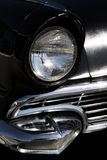 Classic old sixties black car front headlight and grill Royalty Free Stock Photo