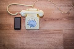 Old Vs New. Classic old telephone next to modern smartphone royalty free stock photo