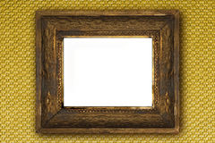 Classic old wooden picture frame carved by hand on gold wallpaper. Classic old wooden picture frame carved by hand on gold effect wallpaper background Royalty Free Stock Photography