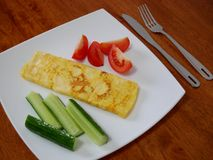 Classic omelet with tomatoes and cucumbers on the white plate.. Fresh breakfast Stock Image