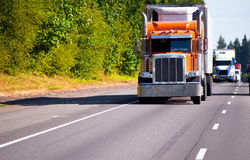 Classic orange semi truck reefer trailer on high way. Classic orange semi truck with a refrigerator on a multilane highway road ahead of a convoy of trucks with Stock Image