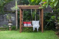 Classic outdoor wooden swing in the green garden with pillows and blanket. Classic outdoor wooden swing in the green garden with pillows and blanket Stock Images